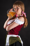 Beautiful woman Oktoberfest drinks beer. Isolated on black Stock Images