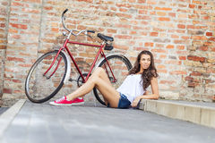 Beautiful woman with old bike in front of a brick wall stock image