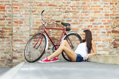 Beautiful woman with old bike in front of a brick wall royalty free stock photo