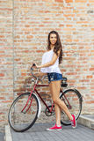 Beautiful woman with old bike in front of a brick wall royalty free stock photography