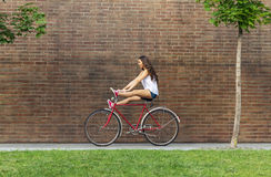 Beautiful woman with old bike in front of a brick wall Stock Photo