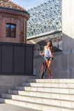 Beautiful woman with old bike in front of the city building Royalty Free Stock Photos