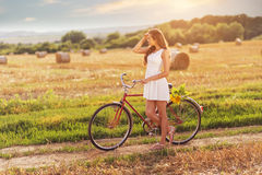 Beautiful woman with old bike in a wheat field Stock Photos