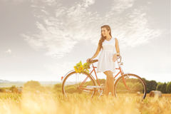 Beautiful woman with old bike in a wheat field Stock Images