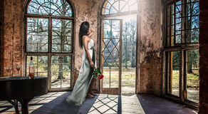 Beautiful woman in an old building with a rose. And a piano with a bottle of wine and two glasses Stock Photo