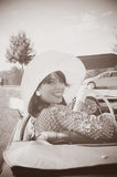 Beautiful woman and old car, fifties style. Young beautiful woman in sixties style on the road trip, old car, sepia Royalty Free Stock Photography