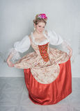 Beautiful woman in old-fashioned medieval dress doing curtsy Royalty Free Stock Photography