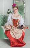 Beautiful woman in old-fashioned medieval dress on the sofa Royalty Free Stock Photos