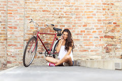 Beautiful woman with an old red bike-phone - in front of the brick wall Stock Photos