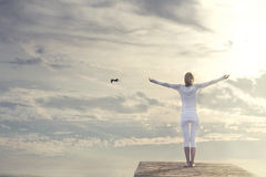 Beautiful woman with open arms meditating in front of a spectacular sky Stock Photography