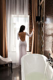 Beautiful woman open the curtain and preparing to take a bath.  Royalty Free Stock Image