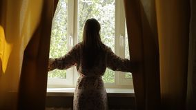 Beautiful woman opening curtains and looking through the window. stock footage