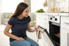 Beautiful woman opening door of oven with buns in kitchen stock photography