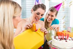 Beautiful woman opening a gift box while celebrating her birthda. Portrait of a beautiful women opening a surprise gift box wrapped in yellow paper while stock image