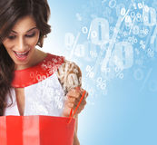 Beautiful woman opening a red shopping bag Stock Images