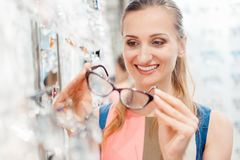 Beautiful woman in optician store chooses her glasses Stock Photo