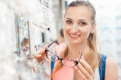 Beautiful woman in optician store chooses her glasses royalty free stock image