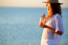 Beautiful woman with orange juice in disposable cup against the sea Stock Photos