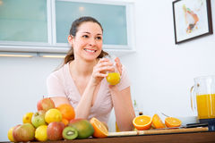Beautiful woman with orange Juice in the kitchen Stock Photos