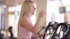 Beautiful woman on orbitrek elliptical trainer stock footage