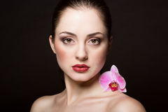 Beautiful woman with orchid flower Royalty Free Stock Photos
