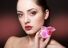 Beautiful woman with orchid flower Royalty Free Stock Images