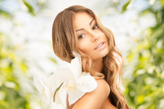 Beautiful woman with orchid flower Stock Images