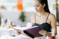 Beautiful woman ordering from menu Stock Image