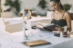 Beautiful woman ordering from menu. In restaurant Royalty Free Stock Image