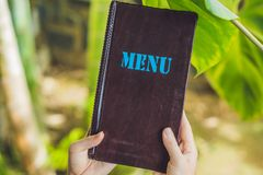 Beautiful woman ordering from menu in restaurant and deciding wh. At to eat Royalty Free Stock Photos