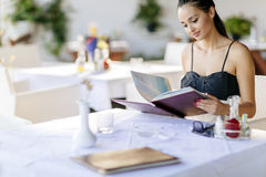 Beautiful woman ordering from menu. In restaurant and deciding what to eat Stock Photos
