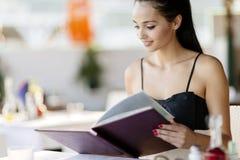 Beautiful woman ordering from menu Stock Images