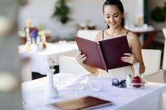 Beautiful woman ordering from menu Stock Photos