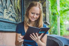 Beautiful woman ordering from menu in restaurant and deciding what to eat Stock Photography