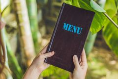 Beautiful woman ordering from menu in restaurant and deciding what to eat.  Stock Images