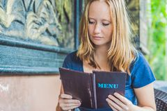 Beautiful woman ordering from menu in restaurant and deciding wh. At to eat Royalty Free Stock Image