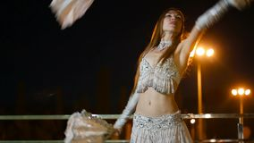 Beautiful woman in oriental costume is dancing fan dance at night outdoor stock video