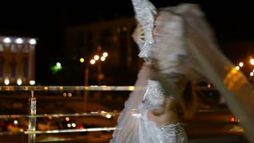 Beautiful woman in oriental costume is dancing fan dance at night outdoor stock video footage