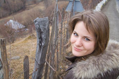 Beautiful woman outdoor. Beautiful young woman on a side of the road near a countryside fence royalty free stock photo