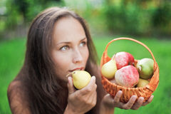 Beautiful woman outdoor with apples and pears. In the crib royalty free stock photography