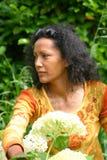 Beautiful woman outdoors in garden. Beautiful woman outdoors working in her garden Stock Photo