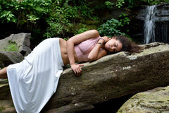 Beautiful woman outdoors - next to waterfall Royalty Free Stock Images