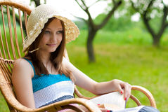 Beautiful woman outdoors relaxing in rocking chair Stock Photo