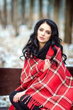 Beautiful woman outdoors is sitting on bench with red plaid. Winter. Young model girl enjoying weather. Fashion model. Nice makeup and hairstyle Stock Photography