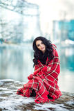 Beautiful woman outdoors is sitting on pier with red plaid. Winter. Young model girl enjoying weather. Fashion model. Nice makeup and hairstyle Stock Photo