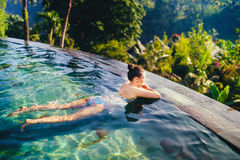 Beautiful woman in outdoors swimming pool. Holiday concept with woman sunbathing in infinity swimming pool royalty free stock photos