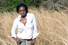 Beautiful Woman Outdoors in Tall Grass (10). A lovely young black woman outdoors, standing in tall grass.  Generous copyspace on frame right Royalty Free Stock Image