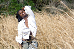 Beautiful Woman Outdoors in Tall Grass (11). A lovely young black woman outdoors, standing in tall grass.  Generous copyspace on frame right Stock Photos
