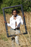Beautiful Woman Outdoors in Tall Grass (12). A lovely young black woman outdoors, standing in tall grass, holding a large black picture frame Royalty Free Stock Images