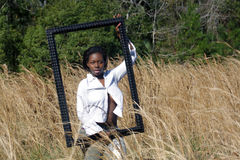 Beautiful Woman Outdoors in Tall Grass (15). A lovely young black woman outdoors, standing in tall grass, holding a large black picture frame.  Generous Royalty Free Stock Images